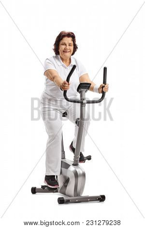 Elderly woman riding an exercise bike isolated on white background