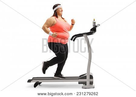 Full length profile shot of an overweight woman running on a treadmill isolated on white background