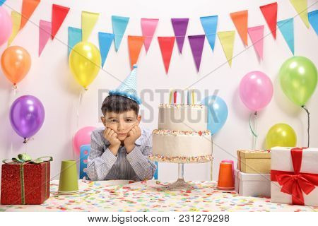 Sad and lonely little boy with a party hat and a birthday cake