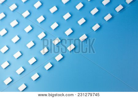White Sugar Cubes Arranged In Diagonal Lines On Blue Background. Top View