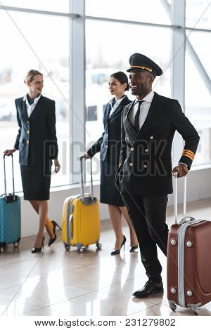 Young Pilot And Stewardesses With Luggage Walking By Airport