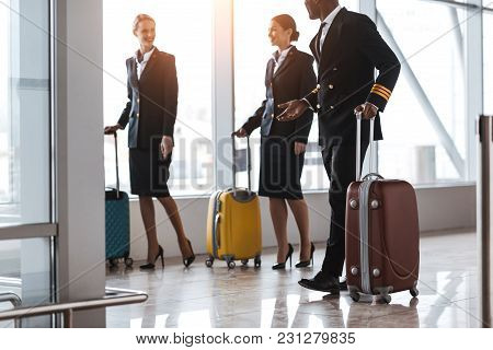 Pilot And Stewardesses With Luggage Walking By Airport