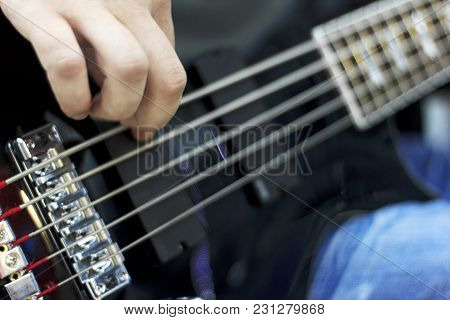 Close Up On The Fingers Of Musician Playing Bass Guitar On The Stage.