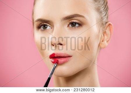 Beauty Concept - Woman Applying Red Lipstick With Pink Studio Background. Beautiful Girl Makes Makeu