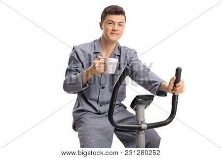 Teenage boy in pajamas riding an exercise bike and holding a cup isolated on white background