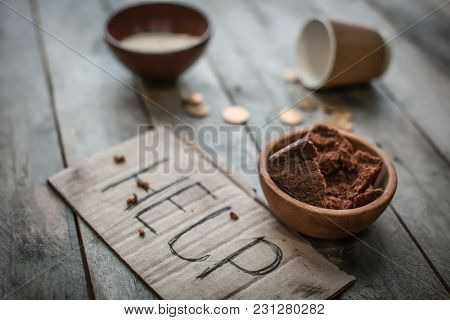 Piece of cardboard with word HELP and food on wooden background. Poverty concept