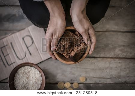 Poor woman holding bowl with bread, closeup