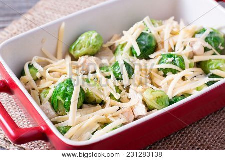 Casserole With Brussels Sprouts And Cheese On A Wooden Table