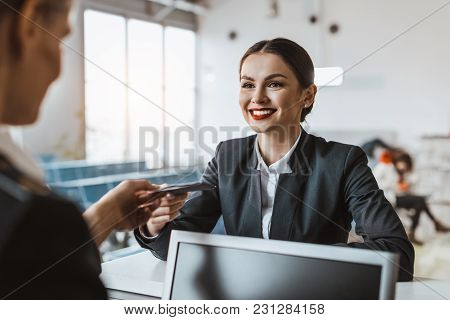 Attractive Young Businesswoman Giving Passport And Ticket To Staff At Airport Check In Counter