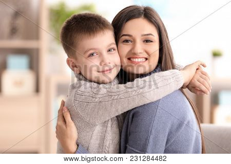 Young woman with little boy indoors. Child adoption