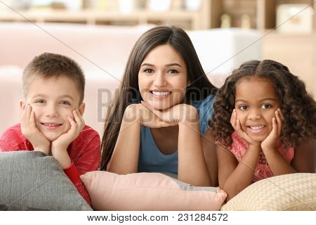 Young woman with little kids indoors. Child adoption