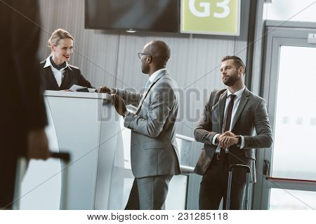 Queue Of Businessmen At Airport Reception To Buy Tickets