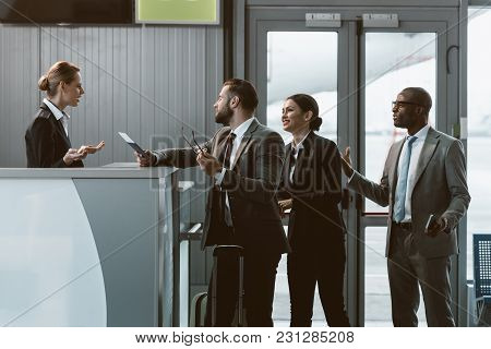 Group Of Dissatisfacted Businesspeople Having Argument With Airport Receptionist