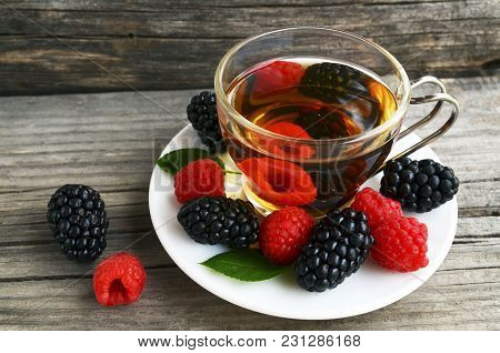 Raspberries And Blackberries Tea With Fresh Picked Berries In A Glass Transparent Cup On Old Wooden