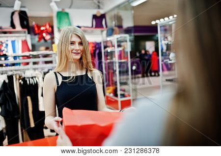 The Seller In The Boutique Gives Shopping Bags With Clothes To The Buyer.