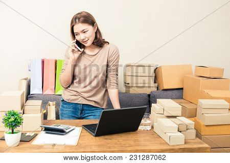 Young Happy Asian Online Business Woman In Her Home Talking To Her Customer On Her Phone While Looki
