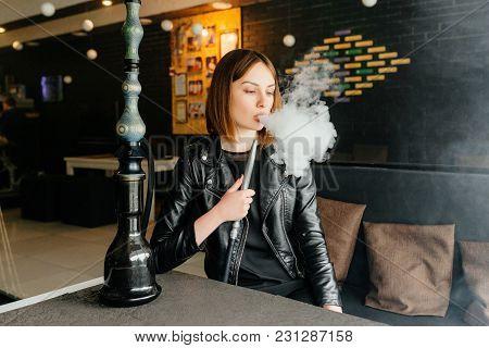 Modern Young Girl Smokes A Hookah In A Hookah Bar.