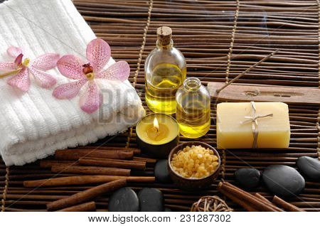 Spa setting with orchid, oil, soap ,stones. Towel on mat background