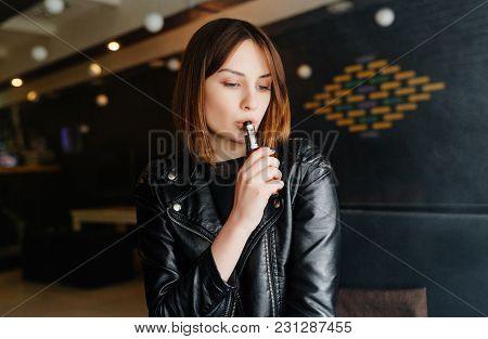 Beautiful Brunette Smoke Electronic Cigarette In A Bar. Vapor Concept.