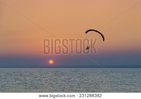 Silhouette Of Powered Paraglider Soaring Flight Over The Sea Against Marvellous Orange Sunset Sky. P