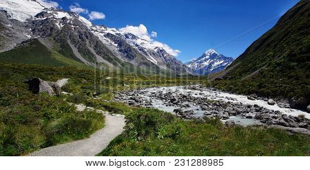 Beautiful Natural Landscape. Rocks, River And Snowy Mountains In The Background. Walking The Hooker