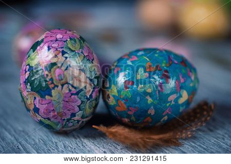 closeup of some homemade decorated easter eggs, made by myself, on a gray rustic wooden table sprinkled with feathers of different colors