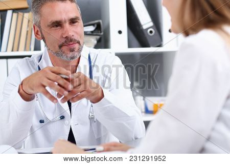Smiling Handsome Mature Doctor Communicate With Patient Holding Silver Pen And Pad. Physical Agreeme