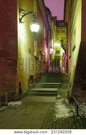 Beautiful Narrow Street With Stairs In Old Town During Evening Blue Hour, Warsaw, Poland.