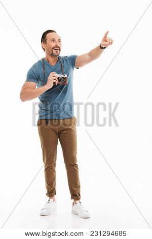 Full length portrait of a happy mature man dressed in t-shirt holding photo camera and pointing finger away isolated over white background