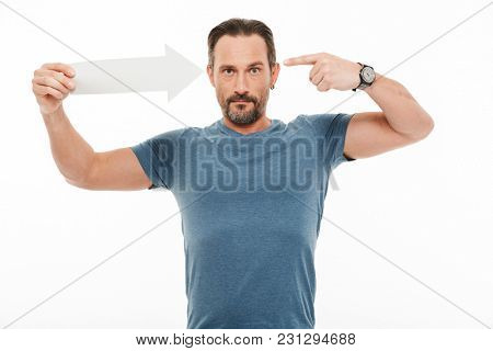 Portrait of a happy mature man dressed in t-shirt pointing at himself with an arrow isolated over white background