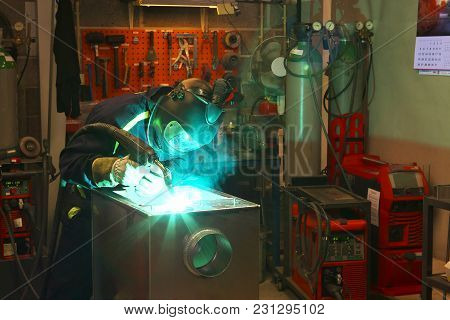 Welder Woking, Background Full Of Different Tools.