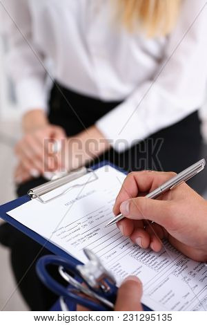 Male Doctor Arm Hold Silver Pen Filling Patient Complaints List Clipped To Pad. Physical Exam Er Dis