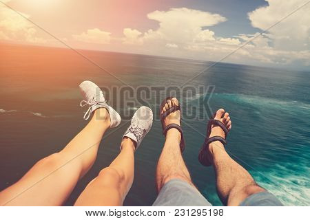 Legs Of Man In Sandals And Woman In Sport Shoes Sitting Above Blue Ocean, Intentional Sun Glare
