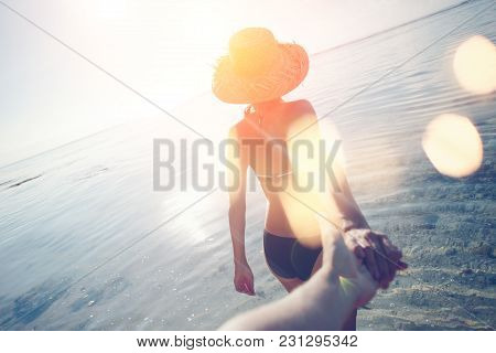 Young woman in hat guiding a man by the hand into the ocean, intentional sun glare and lens flare effects poster
