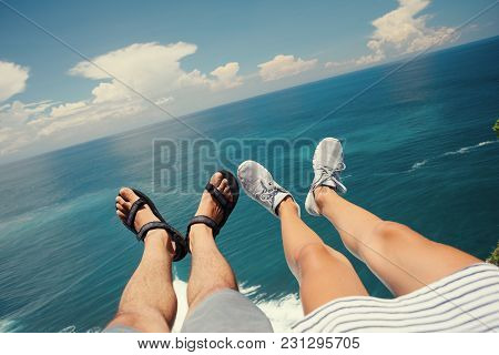 Legs Of Man In Sandals And Woman In Sport Shoes Sitting Above The Ocean