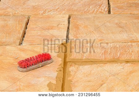 Laying Concrete Outdoor Tiles, Sandstone Colored Paving On The Terrace With Brown Not Dry Joints And