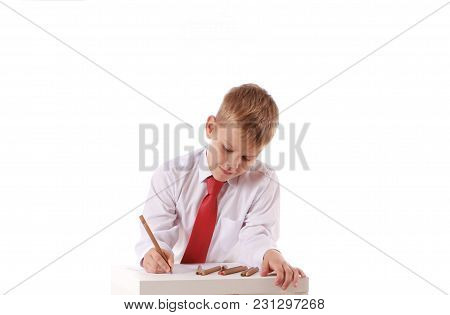 Handsome Schoolboy Is Looking At Camera And Leaning On The Table While Drawing On A White Background