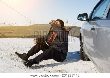 A Drunk Driver Sits On The Ground And Drinks Alcohol From A Bottle.