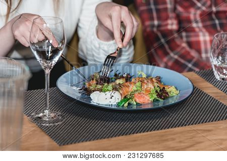 Woman In A White Pullover Eats Delicious Salmon Salad With Egg In A Restaurant At The Food And Wine