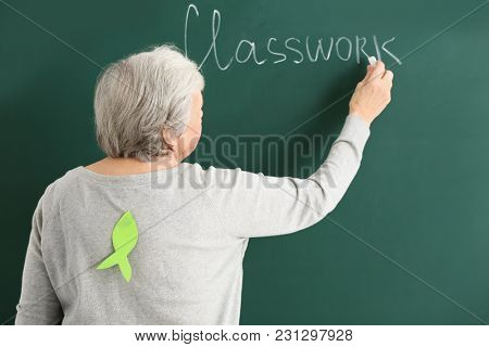 Senior teacher with paper fish on her back writing on chalkboard. April fool's day celebration