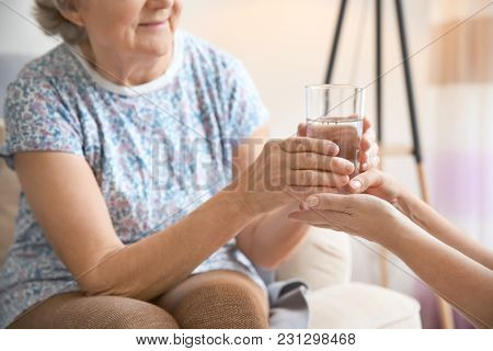 Caregiver giving glass of water to senior woman at home, closeup