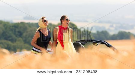 Two women sitting on hood of convertible car having summer trip