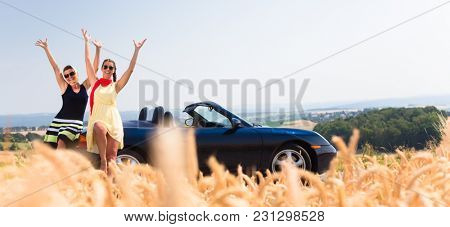 Women having joyride in convertible car having rest at grain field enjoying the landscape