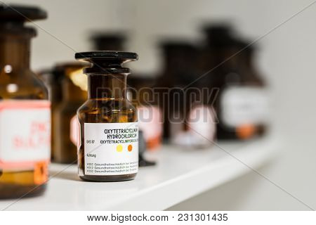 Close-up of the labeled glass container of a chemical pharmaceutical substance on a shelf, next to various supplies in the storage of a modern drugstore
