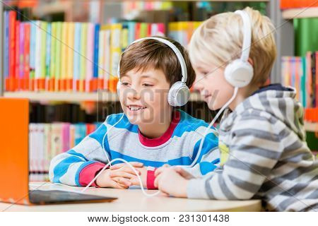 Children in a library listening to audio books with headphones