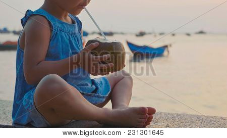 Crop Of Little Cute Girl Drinks Coconut Water With Drinking Straw At Seafront With The Sea And Fishi