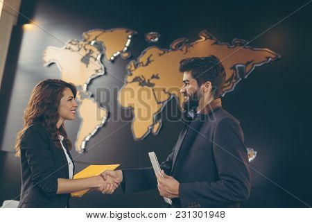 Businessman And Business Woman Having A Conversation In A Modern Office Building