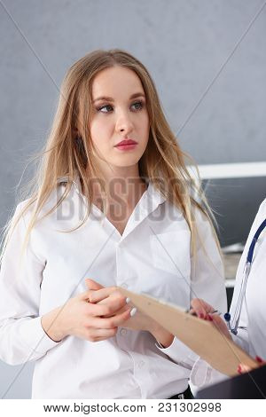 Female Doctor Arm Hold Silver Pen Filling Patient Complaints List Clipped To Pad. Physical Problem E