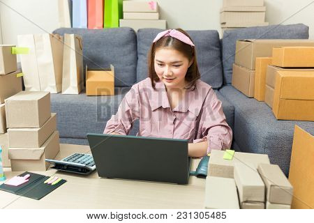 Young Happy Asian Online Business Woman Working On Her Computer At Home In Her Living Room Surrounde