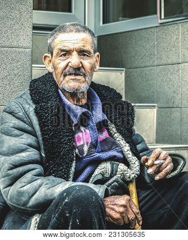 Old Poor And Homeless Gypsy Man Sitting On The Stairs On The Street Smoking Cigarette And Begging Fo